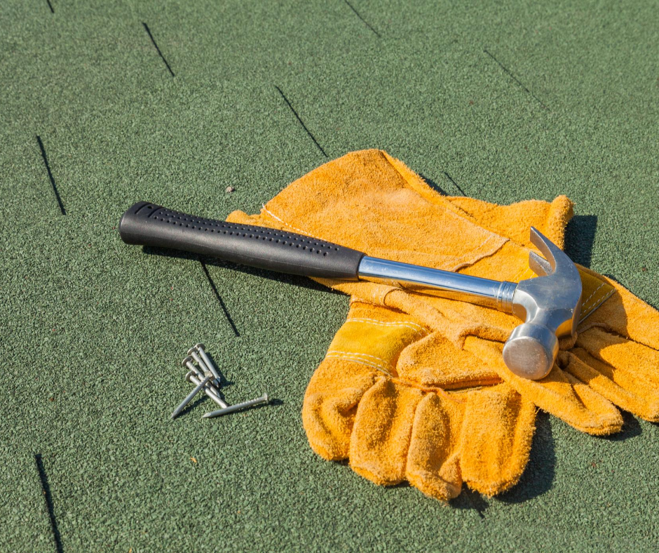 yellow gloves and hammer on green roof