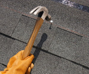 person hammering nail into roof